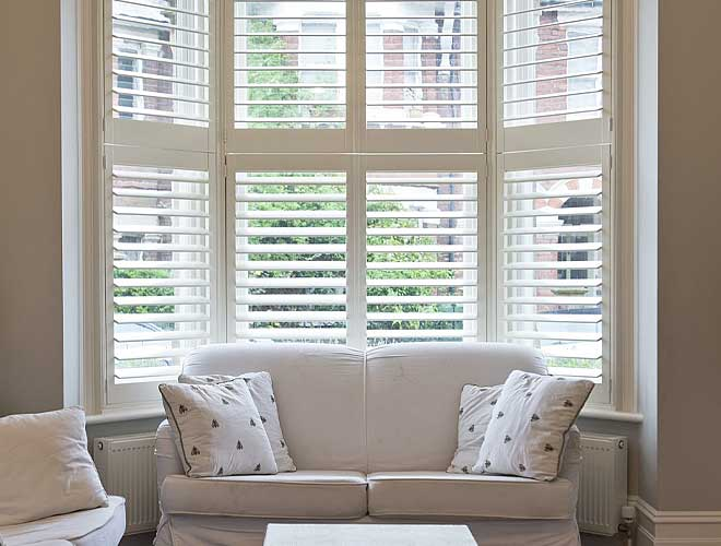 Image of a Bay Window Plantation Shutter in a living room, North West UK by Perfect Blinds